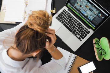 Frau sitzt mit aufgestützten Armen am Laptop